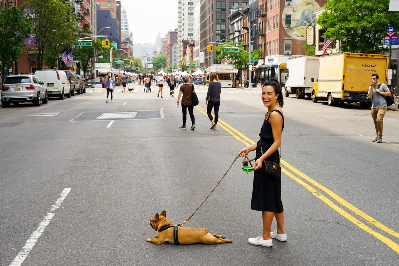 Dog on leash with woman downtown in the middle of the road.