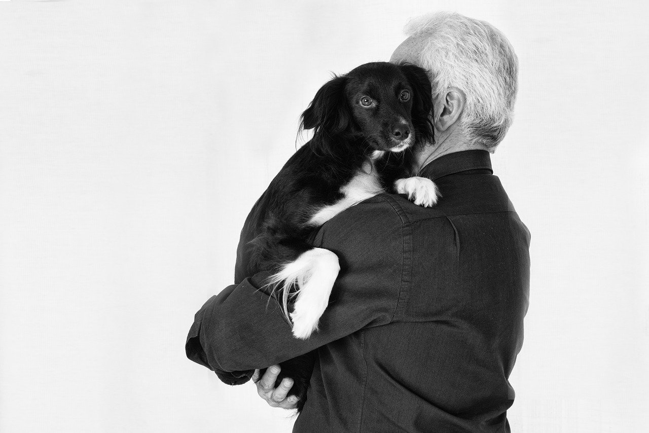 Black and white photo of a man holding a dog.