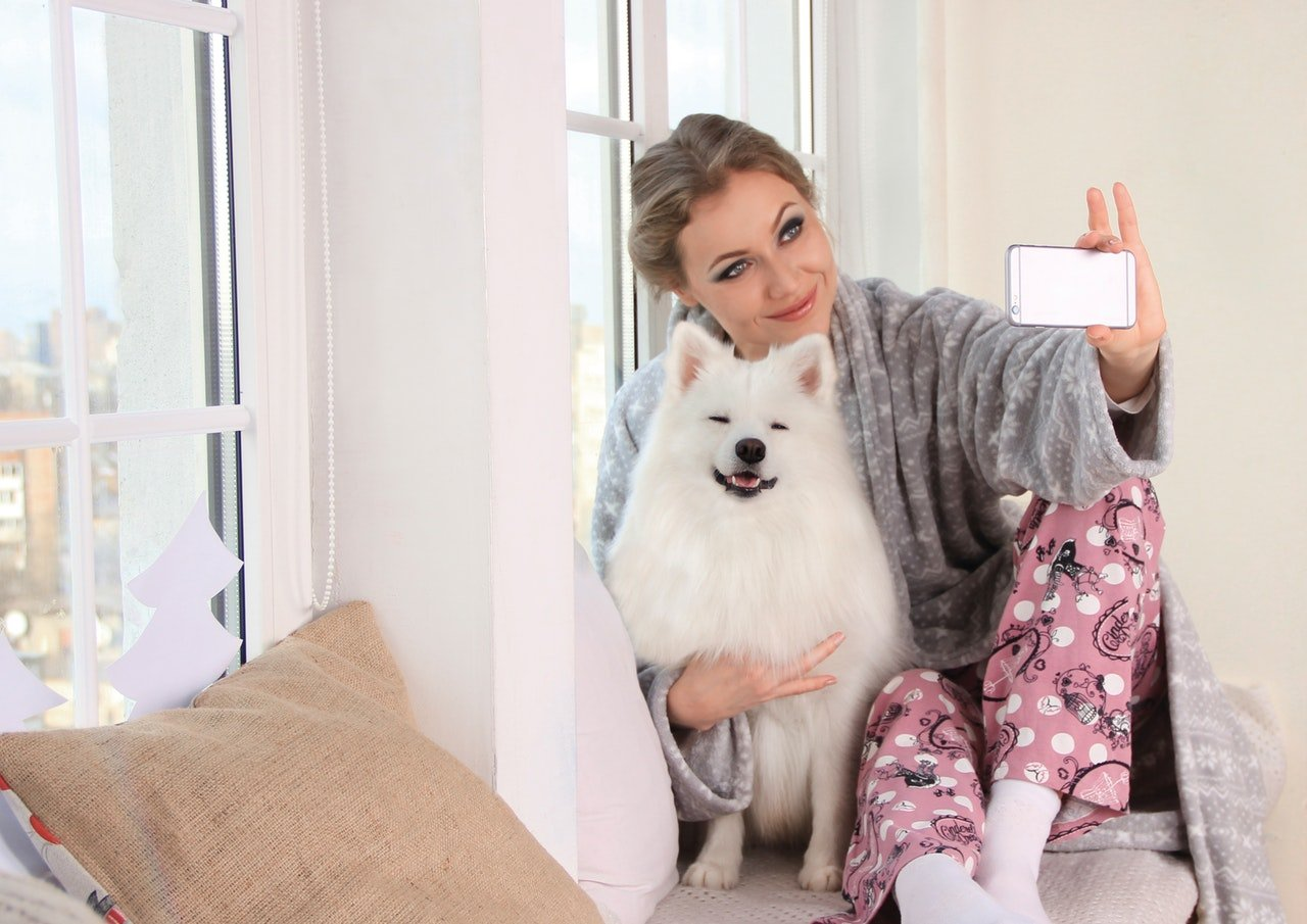 Woman taking a selfie with her white dog in her bedroom.