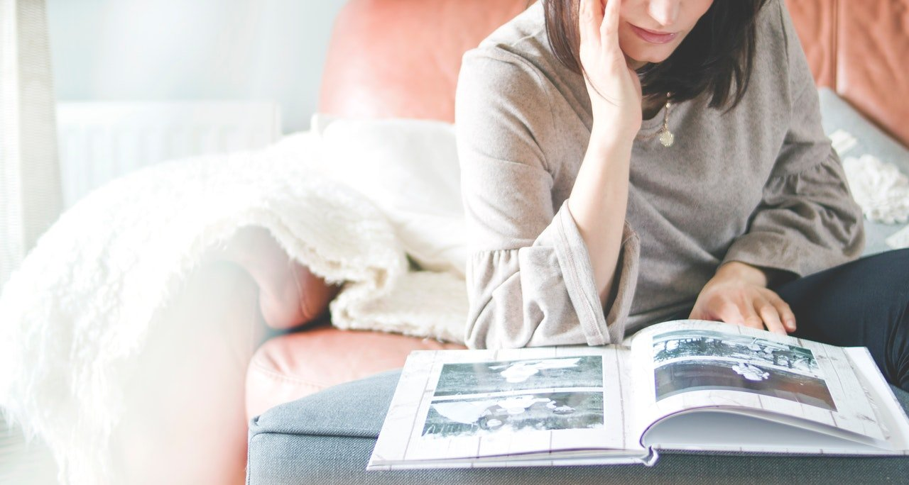 Woman on couch looking at pictures of her pet.