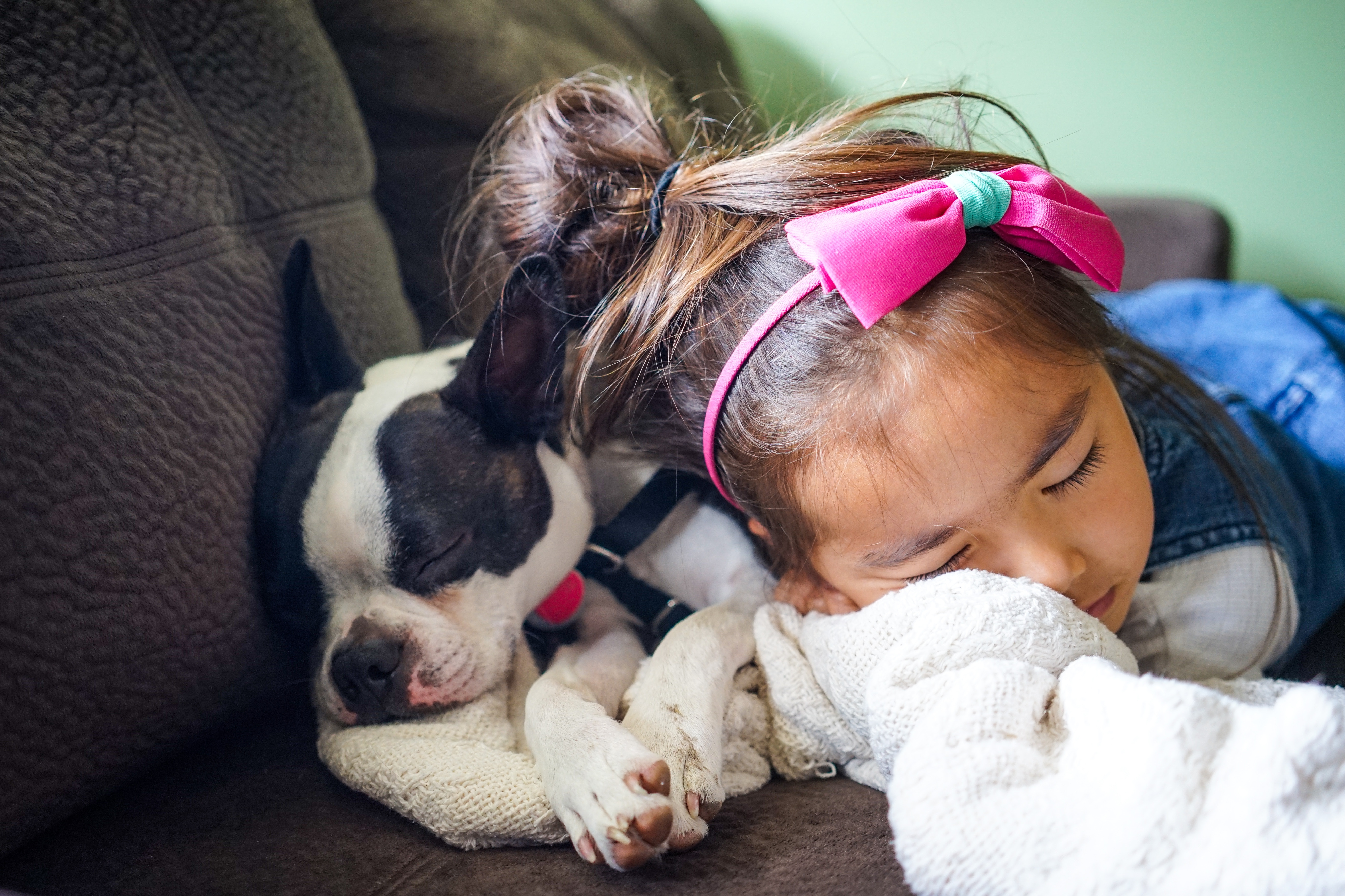 A tired girl and puppy sleeping together on a couch.